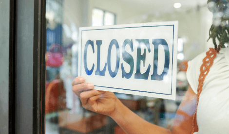 A store owner putting up closed sign on shop door