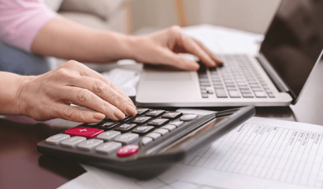 A woman working on tax payments with calculator and laptop