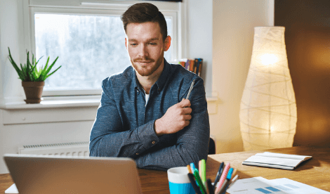 A smart casual looking man thinking in his home office in front of laptop screen