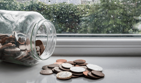 A coin jar by a rainy window that has been tipped over with coins sitting on the window seal