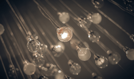 Multiple light bulbs suspended on a dark background signifying purpose statement