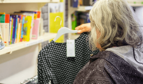 A woman holds up a shirt in a charity shop