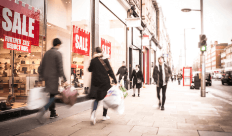 The future of the high street - shoppers walking along street outside sales