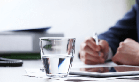 Business man at a desk with glass of water half full