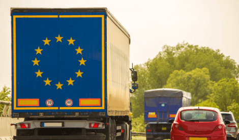 A lorry with the EU logo on the back driving amongst other traffic on a motorway