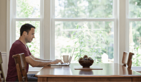 A happy man working from home on dining room table with laptop